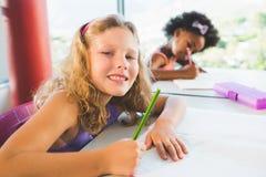 做家庭作业的女孩画象在教室 免版税库存照片