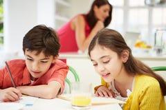 做家庭作业的孩子作为母亲使用膝上型计算机 库存照片