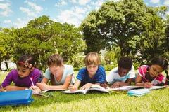 做家庭作业的孩子在公园 库存照片