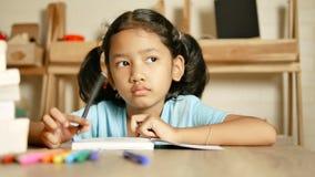 做家庭作业的小女孩和认为某事与微笑 股票视频