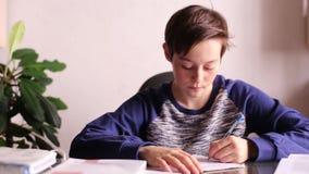 做家庭作业的少年男孩在表上 股票录像