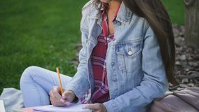 做家庭作业的年轻女性大学生坐校园地面 股票录像