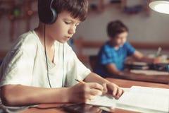 做家庭作业的年轻男孩在书桌 免版税库存图片
