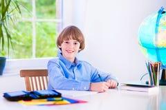 做家庭作业的微笑的逗人喜爱的男孩 免版税图库摄影