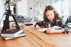 做家庭作业的愉快的学校女孩 写聪明的孩子努力工作和 库存图片