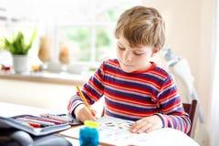 做家庭作业的愉快的微笑的小孩男孩在早晨在学校前在家开始 小孩做 库存图片