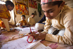 做家庭作业的未知的孩子在Jagadguru学校 库存图片