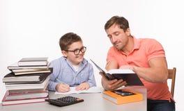 做家庭作业的男孩与他的父亲一起 免版税库存照片