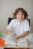 做家庭作业的男孩坐在学校书桌 免版税库存照片
