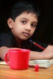 做家庭作业的男孩的画象 免版税库存照片