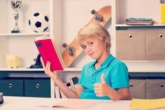 做家庭作业的白肤金发的男孩 免版税库存图片