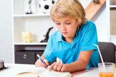 做家庭作业的白肤金发的男孩 图库摄影