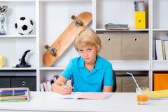 做家庭作业的白肤金发的男孩 免版税图库摄影