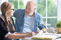 做家庭作业的祖父和孙女 免版税库存照片