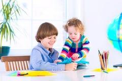 做家庭作业的逗人喜爱的孩子 免版税库存照片