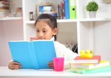 做家庭作业的逗人喜爱的小女孩读书着色呼叫wr 库存图片