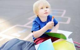 做家庭作业的逗人喜爱的白肤金发的男孩坐校园在有放置的袋子的学校以后近 库存照片