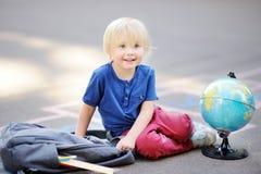 做家庭作业的逗人喜爱的白肤金发的男孩坐校园在有放置的袋子的学校以后近 库存图片