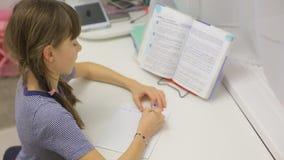 做家庭作业的青少年的女孩坐在桌上 股票视频