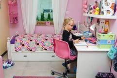 做家庭作业的年轻女小学生 免版税库存图片