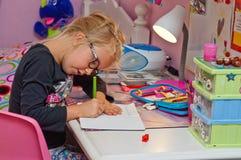 做家庭作业的年轻女小学生 库存照片