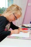 做家庭作业的年轻女小学生 图库摄影