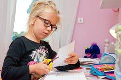 做家庭作业的年轻女小学生 库存图片