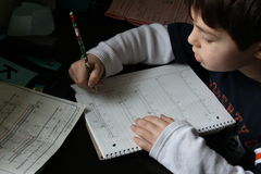 做家庭作业的年轻男孩 库存图片