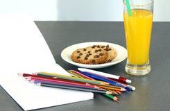 做家庭作业:与空白的笔记本和杯的学校用品橙汁和巧克力曲奇饼 免版税库存照片