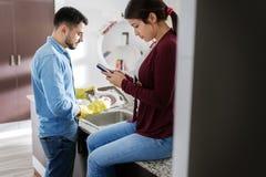 做家庭差事的男人和妇女在厨房里 库存图片