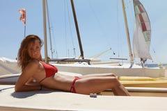 做寒冷的时间海洋海滩的照片女孩 健身活跃妇女消费在Yaht会议公海以后放松 夏天 免版税图库摄影