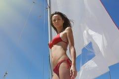 做寒冷的时间Yaht小船的照片年轻性感的女孩 健身活跃妇女消费在水会议公海以后放松 库存照片