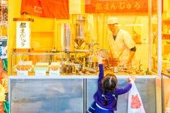 做对快餐商店的注意在Ameya Yokocho著名商店地区的孩子尝试上野区,东京 免版税图库摄影