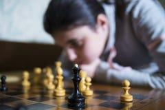 做将死的青少年的女孩下棋 免版税库存照片