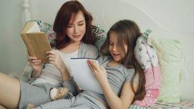 做小学文字的小逗人喜爱的女儿家庭作业在习字簿,当她帮助她时的爱恋的母亲 股票视频