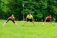 做小组三位年轻的运动员舒展锻炼 免版税库存照片