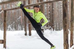 做左腿分裂舒展的适合的女子运动员在森林行使户外 女性体育式样行使的室外冬天公园 库存照片