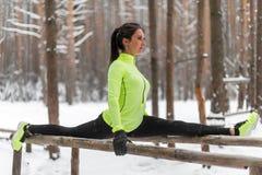 做左腿分裂舒展的适合的女子运动员在森林行使户外 女性体育式样行使的室外冬天公园 免版税库存图片