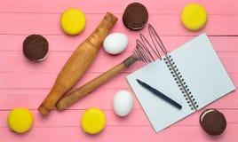做巧克力曲奇饼的过程,蛋白杏仁饼干,在桃红色木背景的成份 鸡蛋,滚针,花冠 免版税库存图片