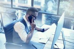 做巨大商业决策现代工作场所的有胡子的商人 工作起始的桌面的年轻人 使用Smartphone 免版税库存照片