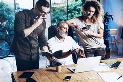 做巨大工作讨论的工友年轻队在现代办公室 有胡子的人谈话与帐户主任和 免版税库存图片