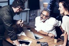 做巨大工作讨论的工友年轻队在现代办公室 有胡子的人谈话与行销经理和 免版税库存照片