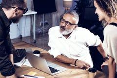 做巨大工作讨论的工友年轻队在现代办公室 有胡子的人谈话与行销经理和 免版税库存图片