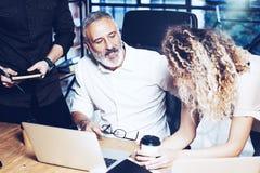 做巨大工作讨论的工友年轻队在现代办公室 有胡子的人谈话与行销经理和 图库摄影