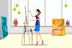 做帆布绘画的美丽的妇女 库存图片