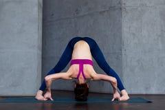 做常设跨骑的运动的少妇实践的瑜伽全长正面图今后弯曲姿势, Prasarita 免版税库存照片