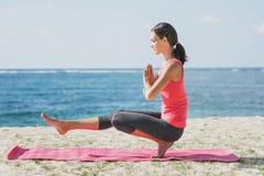 做平衡姿势瑜伽锻炼的运动的妇女 库存照片