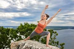 做平衡的一个可爱的少妇瑜伽姿势在岩石 库存图片