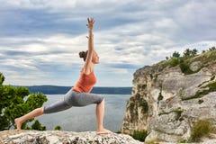 做平衡的一个可爱的少妇瑜伽姿势在岩石 免版税库存图片