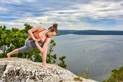 做平衡的一个可爱的少妇瑜伽姿势在岩石 免版税库存照片